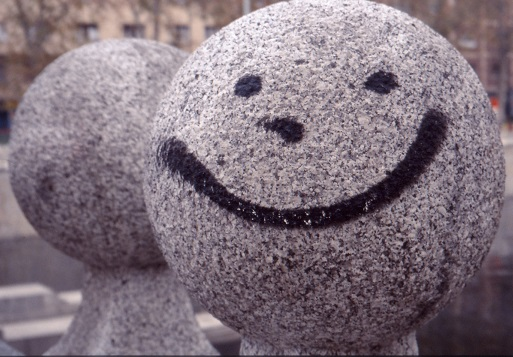 A granite finial with dots for eyes and nose and a large, grinning mouth