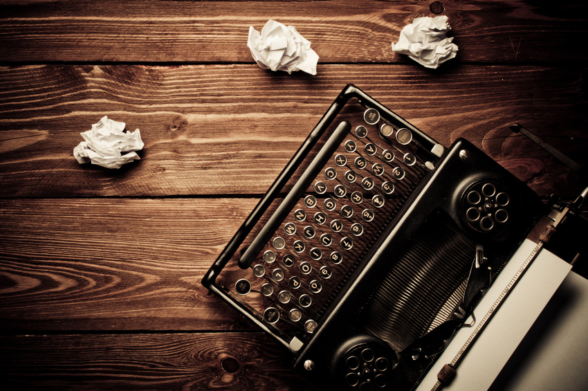 Old-fashioned typewriter surrounded by crumpled paper